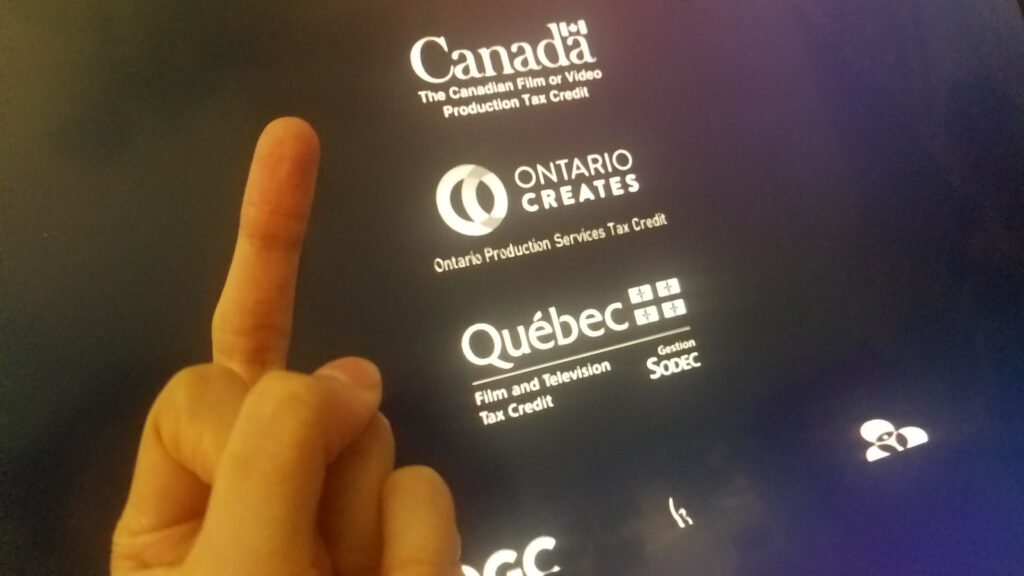 A hand making a middle finger gesture towards a black screen floating various grants and art agencies based in Canada.