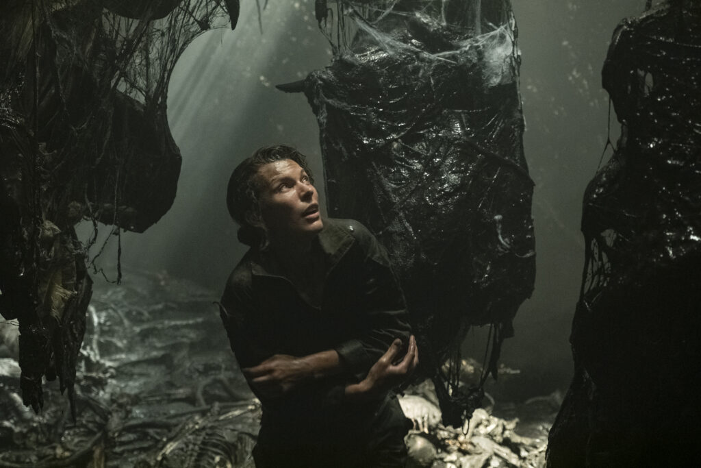 A young, white-passing woman looks around in fear, hugging herself surrounding by slimy, cocoon-like vessels hanging from above in a dark cavern.