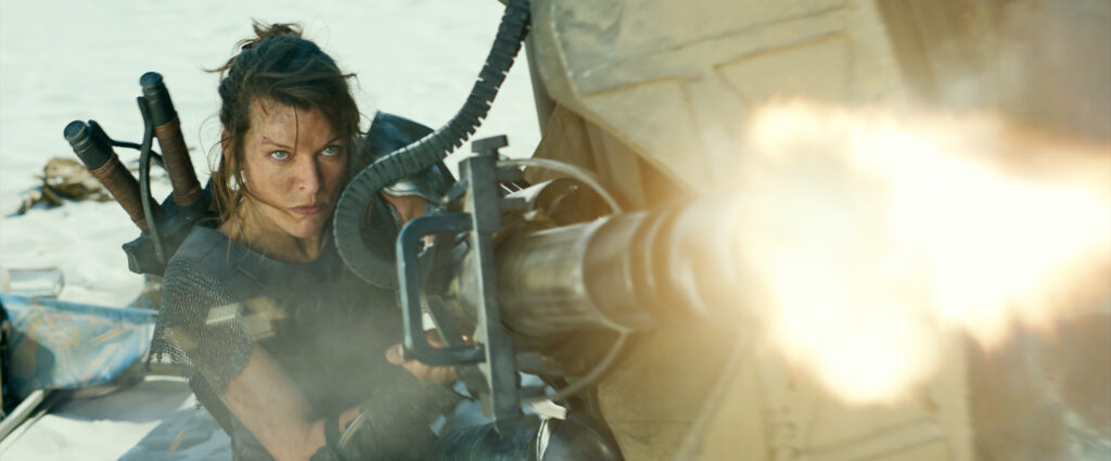 A young, white-passing woman shoots a machine gun with a fierce expression towards a direction off-frame.