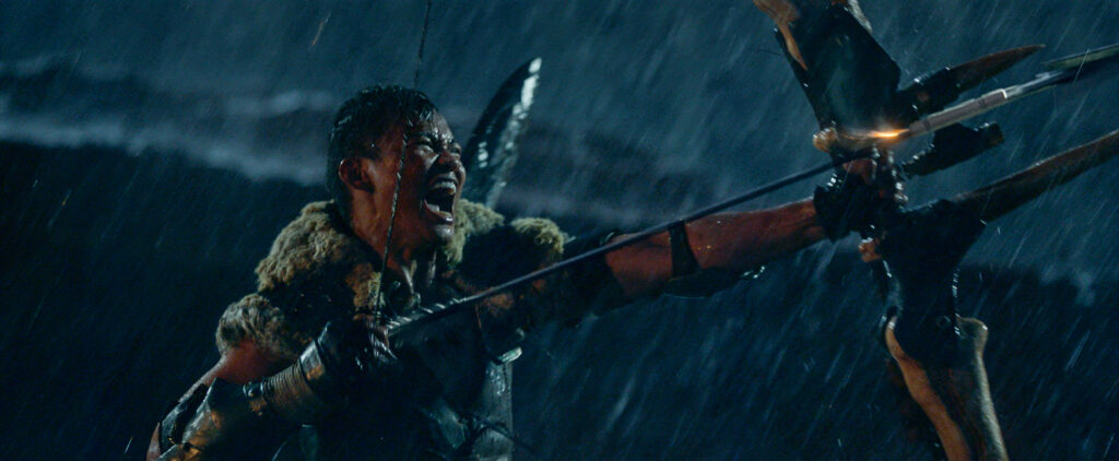 A Southeast Asian presented man wearing leather armor and a fur collar pulls a bow, bearing an aggressive expression mid-shouting as rain pours on him.